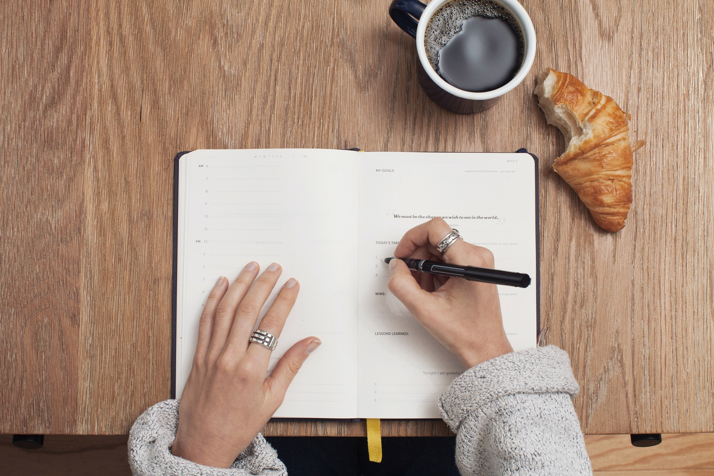 Picutre of a woman at a desk writing in an planner